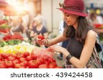 a young woman buying fruits and ... | Shutterstock . vector #439424458