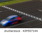 Small photo of Race car racing on speed track with motion blur, Crossing finish line