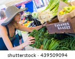 Small photo of Young woman shopping at the local Farmers market.