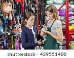 Stock photo saleswoman holding rabbit with girl at pet store 439551400