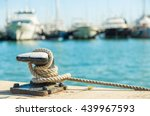 Mooring rope and bollard on sea water and yachts background - stock photo