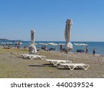 Sunshades and swings on the beach, people relax on the sea coast, Sochi, Russia, June 11, 2016 - stock photo