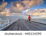 Stock photo australia landscape man walking dog at shorncliffe jetty under cloudy sky 440114290