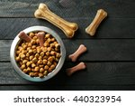 Stock photo dog food in metallic bowl on black wooden background 440323954