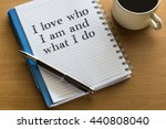 Small photo of I love who I am and what I do - handwriting on a notebook with cup of coffee