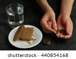 Small photo of brown the bread in a plate on a black background and a trifle in the hands of women near the glass of plain water.The concept of poverty