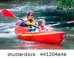 Family on kayaks and canoe tour. Father and child paddling in kayak in a river on a sunny day. Children in summer sport camp. Active preschooler kayaking in a lake. Water fun during school vacation. - stock photo