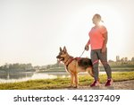 Stock photo happy young woman jogging with her german shepherd dog 441237409