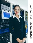 Woman in front of mainframe and communication racks in data-center for large organisation - stock photo