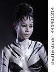 Small photo of Girl in Airbrush Body Paint with Zebra skin art in Black background, low key studio lighting