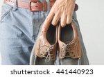 man hand holding shoe. | Shutterstock . vector #441440923