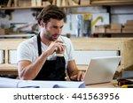 carpenter is using his tablet... | Shutterstock . vector #441563956