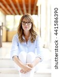 Small photo of Portrait of ageless beautiful woman with eyewear wearing casual clothes while sitting on stairs and looking at camera.