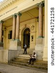 Small photo of HAVANA, CUBA - JUNE 19, 2016: An old man, sitting on the steps of a historic building in La Habana Vieja plays a flute to supplement his meager pension from the Cuban government.