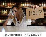 Small photo of drunk alcoholic blond woman drinking whiskey glass asking for help holding message board depressed wasted and sad at bar or pub in alcohol abuse and housewife alcoholism