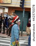 Small photo of COTACACHI, ECUADOR - JUNE 24, 2016: Inti Raymi, the Quechua solstice celebration, with a history of being violent in Cotacachi. Man dressed as an American Indian lags behind.