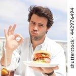 young man eating a hamburger | Shutterstock . vector #442976494