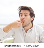 young man eating chips | Shutterstock . vector #442976524