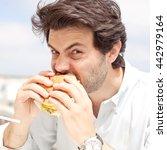 young man eating a hamburger | Shutterstock . vector #442979164