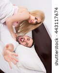 Small photo of Portrait of young shocked adults caught during adultery in bedroom. Focus on man