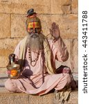 Small photo of Hindu sadhu holy man, sits on the ghat, seeks alms on the street in Jaisalmer, Rajasthan, India . Close up
