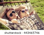 Father And Son Lying On Hammock ...