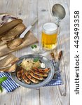 Small photo of Bavarian beer garden meal - Fried sausages from Nuremberg with sauerkraut and horseradish traditionally served on a pewter plate with hearty farmhouse bread and a tankard of cold Munich lager beer
