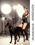 Small photo of Attractive young woman in fitting leather suit alluring with her beautiful dog at studio in the light flashes. Fashion shot.