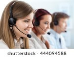 Small photo of Portrait of call center worker accompanied by her team. Smiling customer support operator at work. Help and support concept