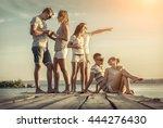 friends sitting on wooden pier... | Shutterstock . vector #444276430