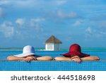 Two Women In A Hat Sitting On...