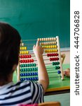 Small photo of Child working with abacus in the classroom