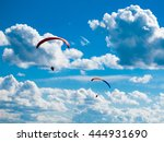 Small photo of Two dark paraglide silhouettes on background of blue summer sky and white clouds. Adrenalin sport theme.