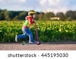 Small photo of Little child learning to ride a scooter in a city park on sunny summer day. Cute preschooler boy in safety helmet riding a roller. Kids play outdoors. Active leisure and outdoor sport for children.