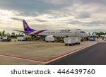 Small photo of Thai airway B737-400 parked with ground services equipment at the parking bay in Samui airport, Thailand on July 26 2016 in late afternoon under a cloudy sky before sunset.