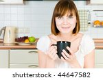 Portrait of a young successful woman, enjoying a cup of coffee in her home. - stock photo