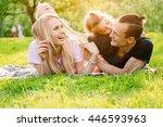 family lying on grass in... | Shutterstock . vector #446593963