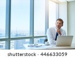 Small photo of Attractive and mature businessman sitting at his desk in a modern office with large windows, looking up and away from his laptop as though he has had a positive idea