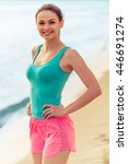 Small photo of Beautiful girl in sport clothes is looking at camera and smiling while standing akimbo on the beach