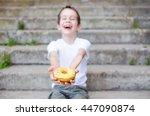 laughing boy holding a donut.... | Shutterstock . vector #447090874