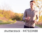 cheerful young jogger running... | Shutterstock . vector #447323488