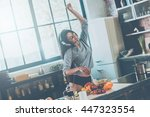 Small photo of Enjoying carefree morning. Beautiful young mixed race woman in headphones cooking salad and dancing while standing in kitchen at home