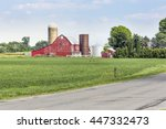 An Old Red Barn With Silos...