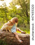 Stock photo little girl kissing pets the girl and a dog sitting on a fallen tree pedigree dogs spitz funny 447455320
