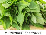 Small photo of Fresh green leaves of amaranthus blitum closeup on wooden surface