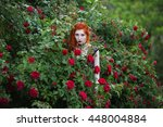 Stock photo gothic girl with red hair near the bushes of purple and red roses in the summer garden fashion 448004884
