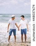 Small photo of Portrait of happy Vietnamese gay couple at the beach