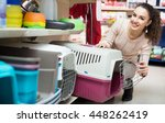 Stock photo portrait of adult girl purchasing pet kennels in petshop 448262419