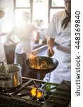 Small photo of Chef tossing stir fry over large flame in commercial kitchen
