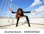 Woman in a black bodysuit and mask cat is protected by claws on the roof under the blue sky with clouds